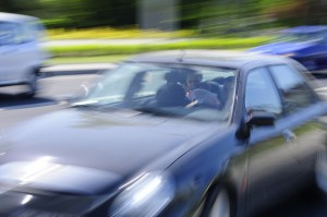 Car racing along in traffic making it appear blurred.