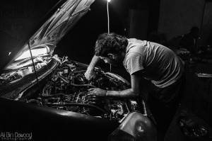 An automobile mechanic working on the engine of a car.