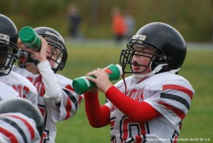 Kids in football uniforms drinking from there water bottles.