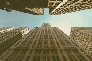 View of tall city buildings from the bottom looking up.