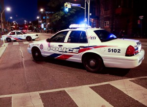 Police cars blocking an intersection at night in Toronto.