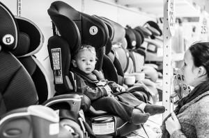 Child being tested in a car seat by his mother.