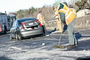 Workers cleaning up the roadway after a car accident.