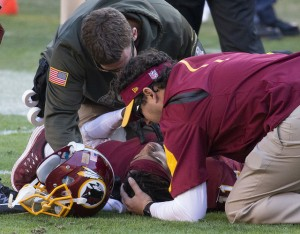 Football player laying on the field and being attended to in case of moderate brain injuries.