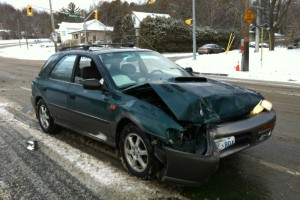 Green car with front end damage from a collision.