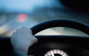 View of car driver with left hand on the steering wheel.